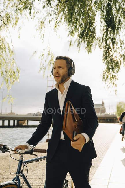 Empresário caminhando com bicicleta na cidade durante o dia ensolarado — Fotografia de Stock