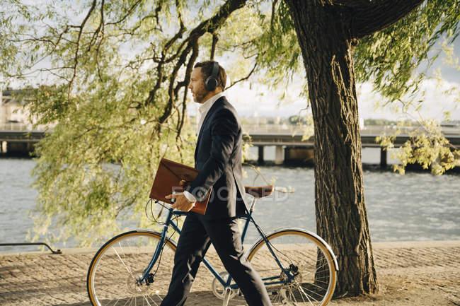 Вид сбоку бизнесмена, идущего с велосипедом по пешеходной дорожке, слушая музыку в наушниках — стоковое фото