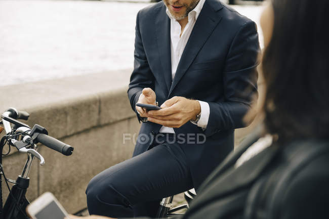 Midsection of businessman using mobile phone while sitting on bicycle by businesswoman — Stock Photo