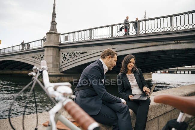 Businessman and businesswoman discussing over laptop while sitting on retaining wall by canal in city — Stock Photo