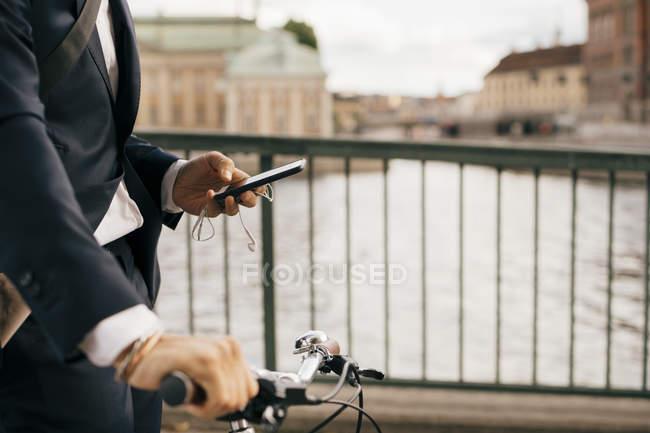 Midsection de hombre de negocios que usa el teléfono móvil mientras camina con bicicleta en el puente en la ciudad - foto de stock