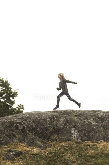 Full length side view of girl running on rock formation against clear sky — Stock Photo