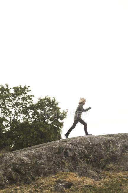 Full length of girl running on rock formation against clear sky — Stock Photo