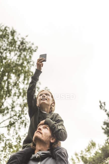 Tiefansicht des Mädchens, das mit dem Handy fotografiert, während es auf den Schultern des Vaters gegen den Himmel sitzt — Stockfoto