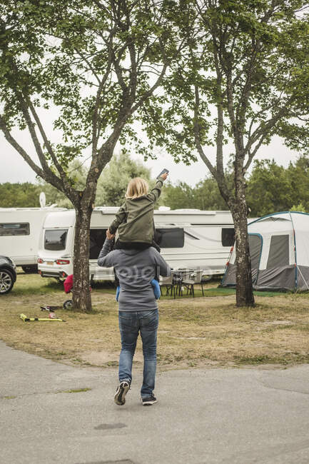 Rear view of father carrying girl on shoulders while standing against camper van — Stock Photo
