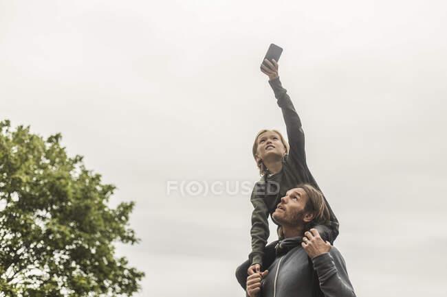 Fille photographiant à l'aide d'un téléphone intelligent assise sur les épaules de son père contre un ciel dégagé — Photo de stock