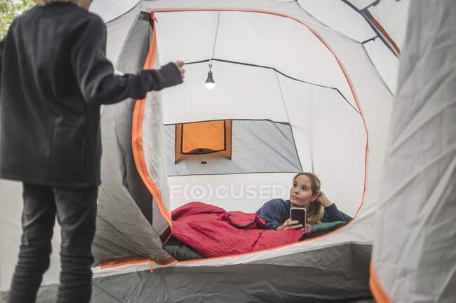 Menina conversando com irmã usando telefone celular na tenda — Fotografia de Stock