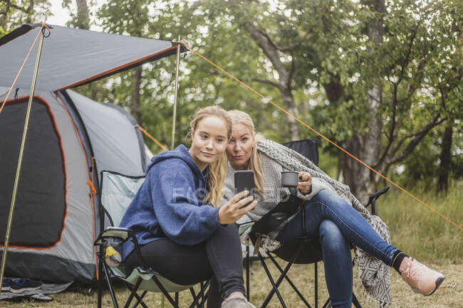 Mother and daughter taking selfie on smart phone while having coffee in campsite — Stock Photo