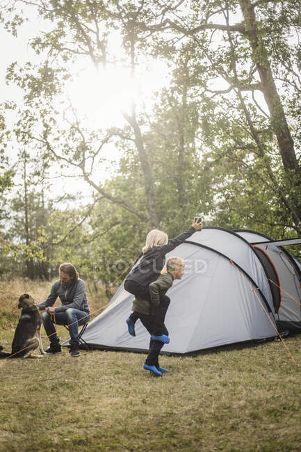 Homme attelé à un chien pendant que des enfants jouent au camping sous tente — Photo de stock