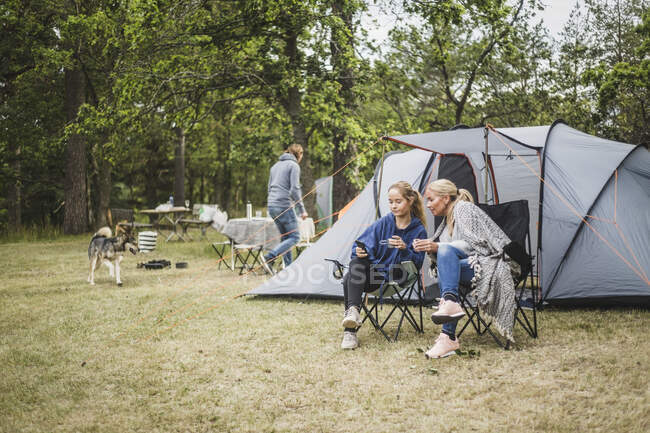 Mother and daughter having coffee while looking at mobile phone in campsite — Stock Photo