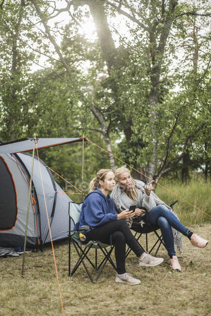Full length of woman talking to daughter while sitting at campsite — Stock Photo