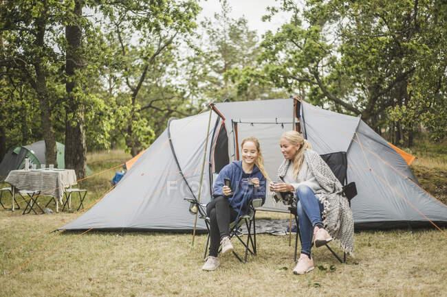 Tochter zeigt Mutter Handy beim Kaffeetrinken vor Zelt — Stockfoto