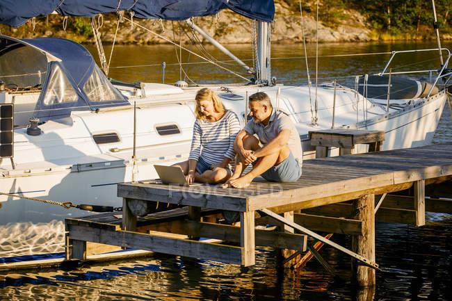 Casal discutindo sobre laptop enquanto sentado no cais por iate durante o dia ensolarado — Fotografia de Stock