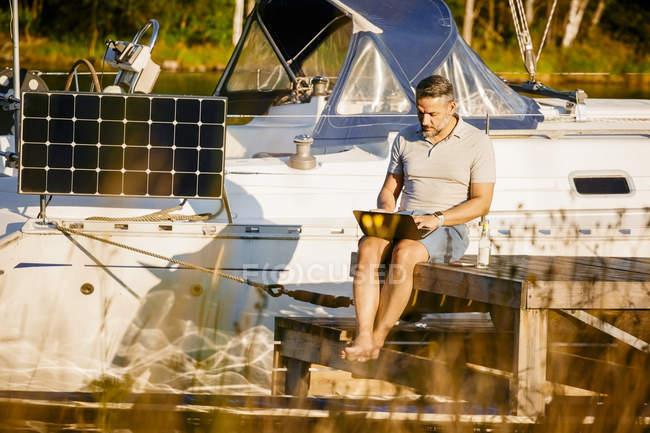 Maduro homem trabalhando no laptop enquanto sentado no cais contra iate sobre lago — Fotografia de Stock