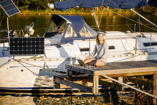 Mujer reflexiva con el ordenador portátil sentado en el muelle por yate amarrado en la orilla del lago soleado - foto de stock