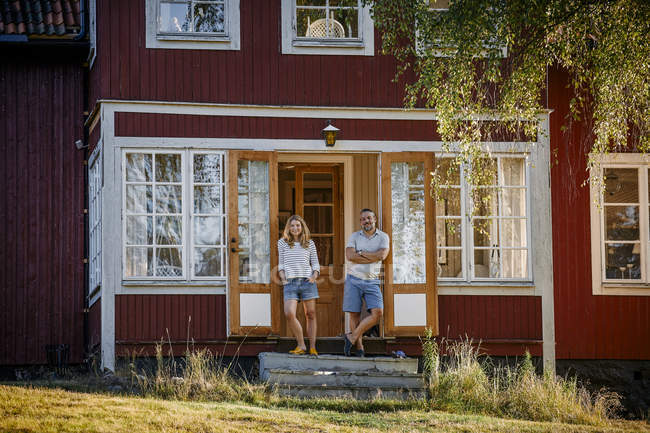 Full length portrait of couple standing at doorway of log cabin — Stock Photo