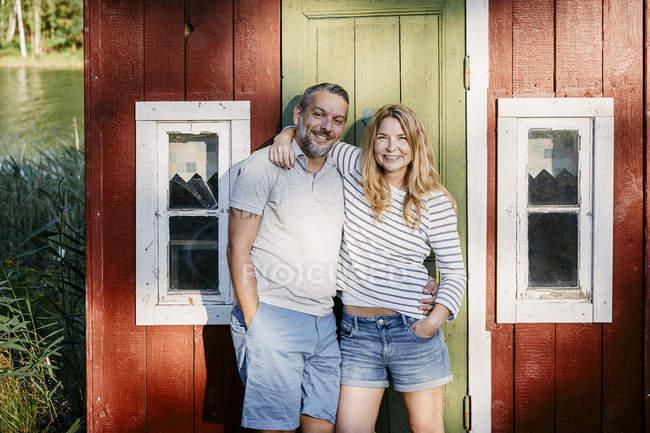Retrato de casal sorridente de pé com braços em volta contra a porta na cabine de log — Fotografia de Stock