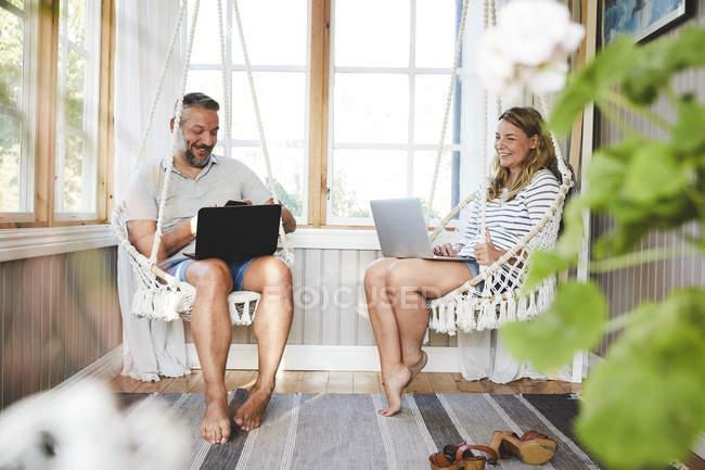 Pareja sonriente que usa computadoras portátiles mientras está sentada en el columpio de cuerda en la cabina de madera - foto de stock