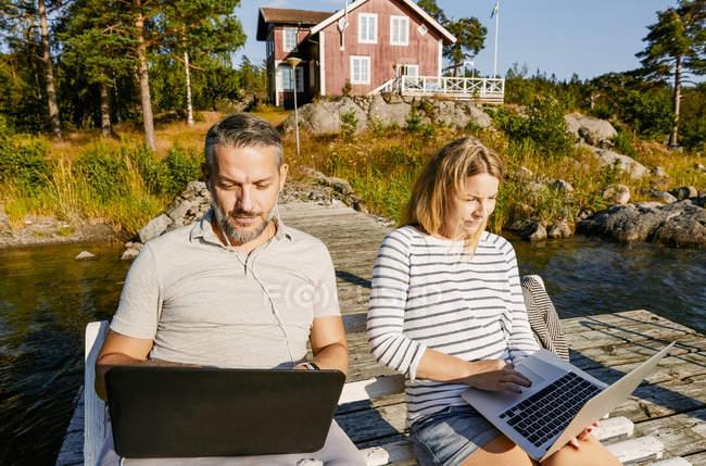 Casal usando laptops enquanto sentado no banco juntos no cais durante o verão — Fotografia de Stock
