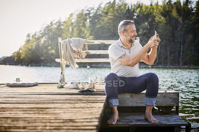 Homem usando fones de ouvido fotografando através de tablet digital enquanto sentado no cais sobre o lago — Fotografia de Stock