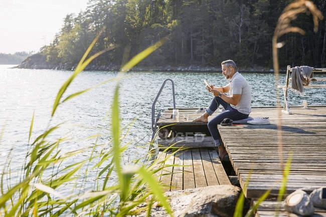 Longitud completa del hombre usando tableta digital mientras está sentado en el muelle de madera sobre el lago en el bosque - foto de stock