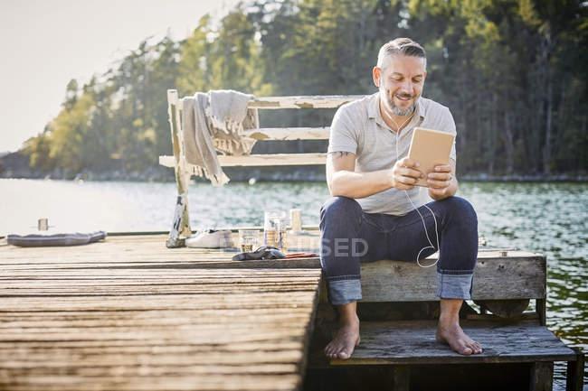 Sorrindo homem maduro usando tablet digital com fones de ouvido enquanto sentado no molhe sobre o lago — Fotografia de Stock
