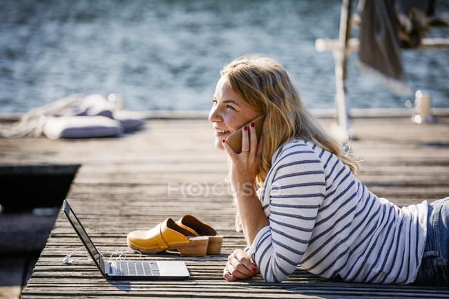 Donna sorridente con computer portatile che parla sullo smartphone mentre giace sul molo di legno — Foto stock