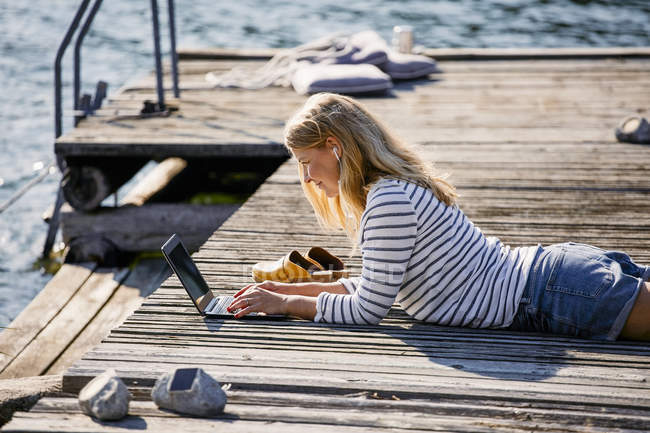 Metà adulto femminile digitando sul computer portatile mentre sdraiato sul molo di legno durante le vacanze estive — Foto stock