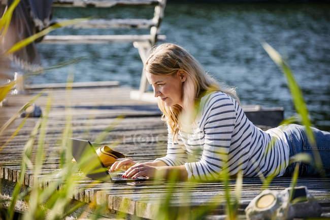 Mujer acostada en la parte delantera mientras trabaja sobre el portátil en el muelle durante el verano - foto de stock