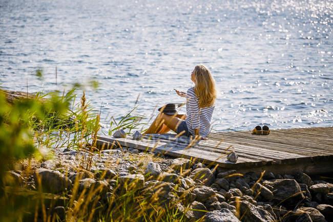 Feminino falando através de smartphone enquanto sentado no molhe sobre o lago — Fotografia de Stock