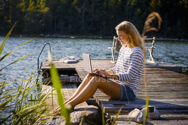 Mujer con auriculares usando el ordenador portátil mientras está sentado en embarcadero contra el lago - foto de stock