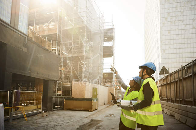 Female engineers in reflective clothing discussing at construction site — Stock Photo