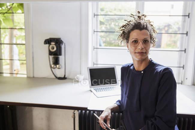 Porträt einer selbstbewussten Architektin, die im Büro am Tisch sitzt — Stockfoto