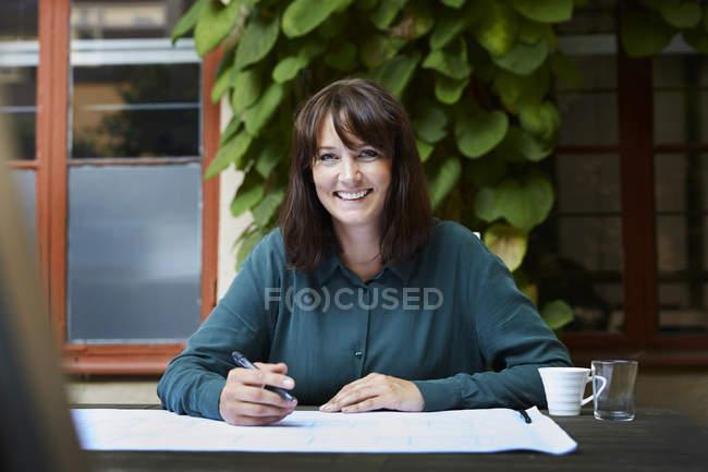 Портрет усмішки архітекторки з кресленнями за столом на задньому дворі. — стокове фото