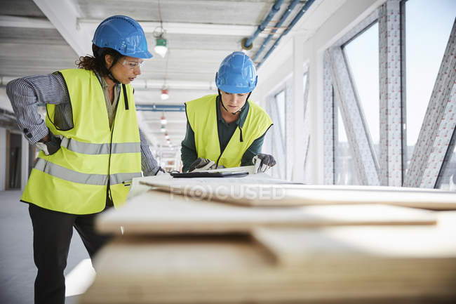 Female architects discussing over blueprint at construction site — Stock Photo