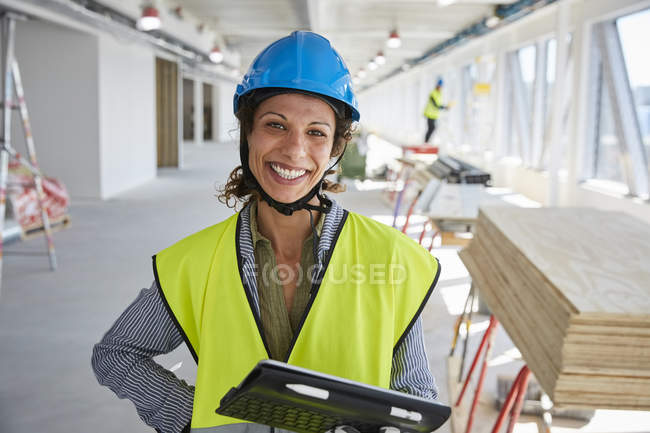 Portrait d'ingénieure souriante avec tablette numérique debout sur le chantier — Photo de stock