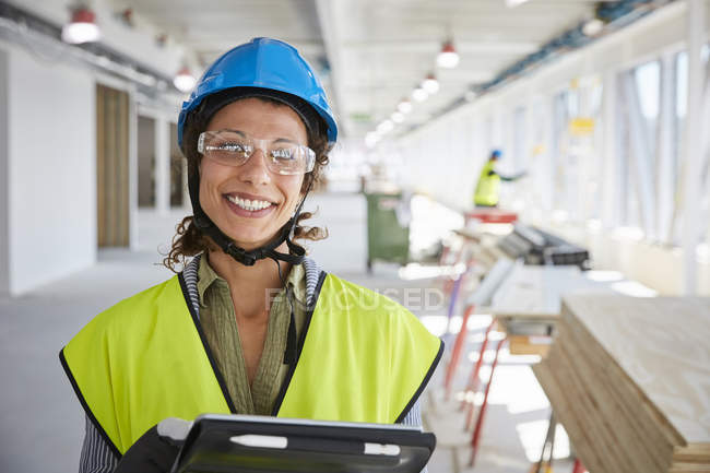 Portrait of smiling female foreman with digital tablet at construction site — Fotografia de Stock