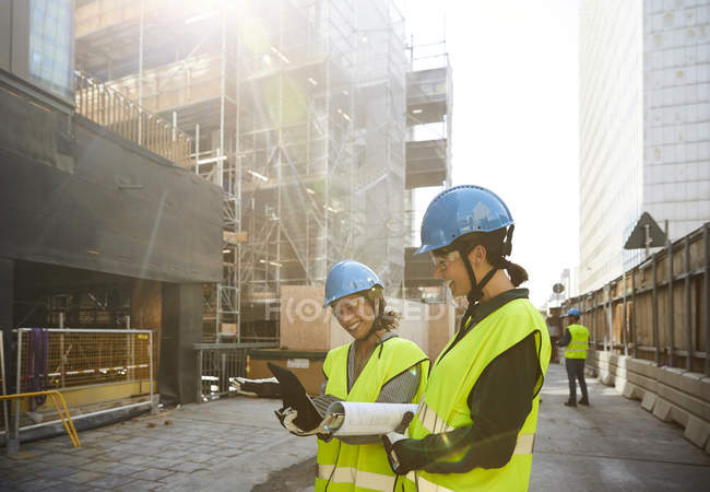 Female engineers discussing over digital tablet at construction site during sunny day — Stock Photo