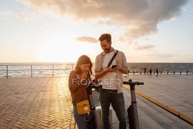 Couple avec des scooters électriques utilisant un téléphone mobile tout en restant sur la promenade pendant le coucher du soleil — Photo de stock