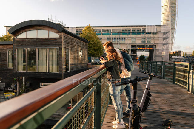 Couple with electric push scooters enjoying on bridge in city against sky — Stock Photo