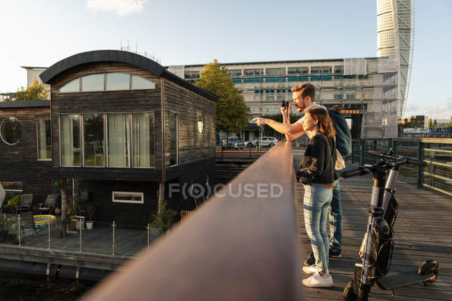 Niveau de surface du couple photographiant debout sur le pont avec des scooters électriques en ville — Photo de stock
