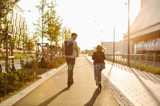 Full length of couple talking while riding electric push scooter on city street during summer vacation — Stock Photo