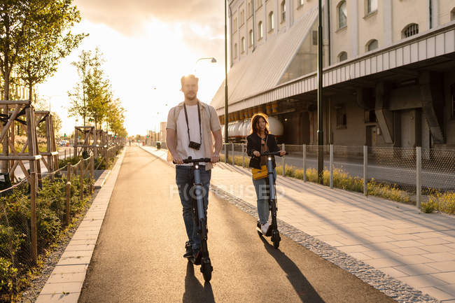 Man and woman riding electric push scooters on road in city during summer — Stock Photo