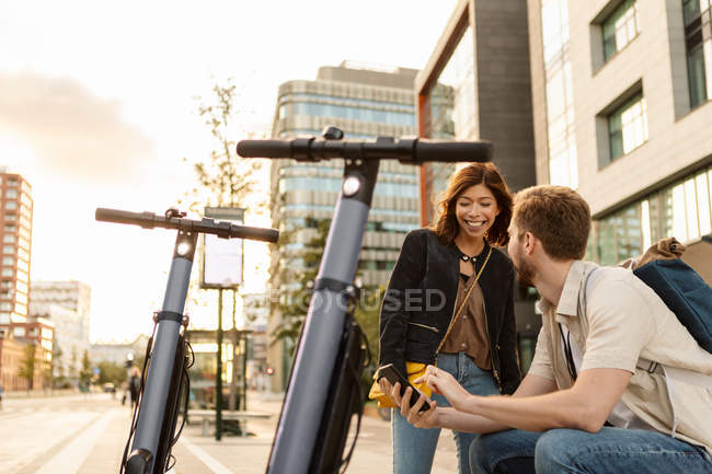 Man showing smart phone to girlfriend while sitting by electric push scooters in city — Stock Photo