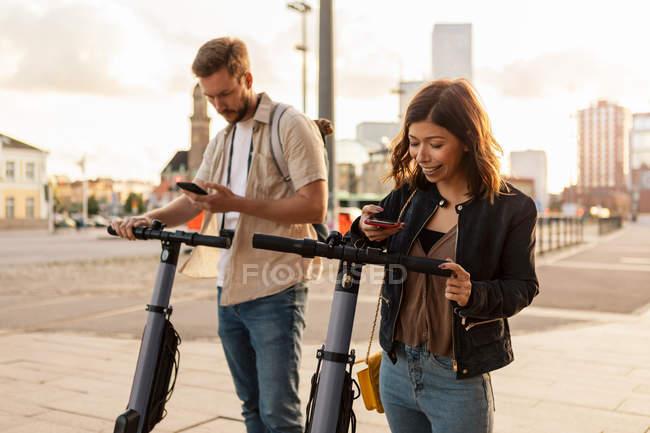 Comutadores masculinos e femininos digitalizando através de telefones celulares enquanto destrava scooters elétricos empurrar na cidade — Fotografia de Stock