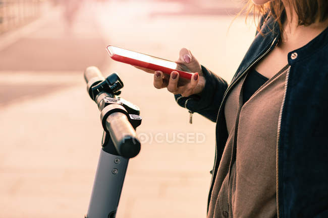 Midsection of woman scanning with mobile phone over electric push scooter — Stock Photo