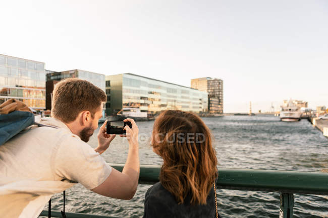 Woman looking at man photographing river on smart phone while traveling in city — Stock Photo