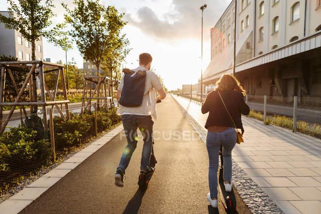 Visão traseira do casal montando scooter elétrico empurrar na rua na cidade durante o dia ensolarado — Fotografia de Stock