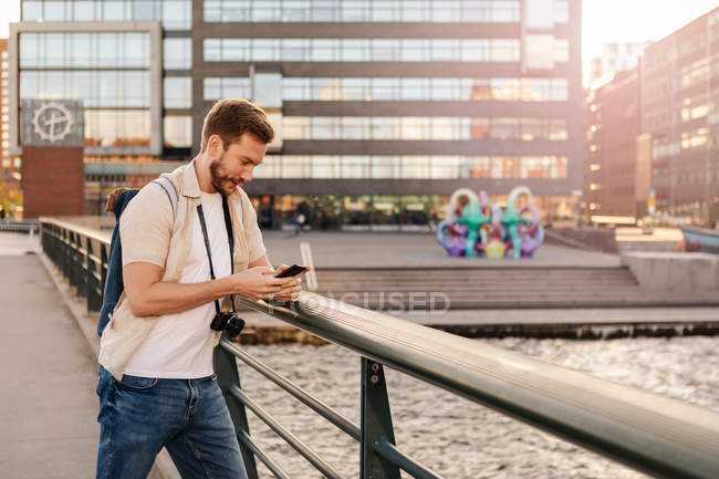 Mid adult man using smart phone while standing by railing in city — Stock Photo