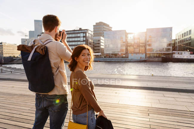 Portrait of smiling woman standing with man photographing city during summer vacation — Stock Photo